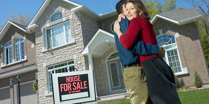couple celebrating buying a house on the front lawn
