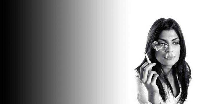 woman depressed smoking in dark place