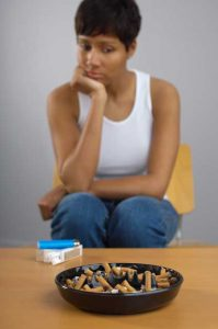 depressed woman looking at cigarette butts